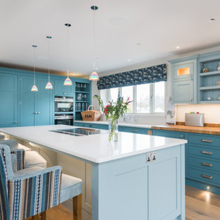 Photo of a large classic l-shaped kitchen in Other with shaker cabinets, blue cabinets, wood worktops, white splashback, medium hardwood flooring, an island, beige floors and beige worktops.