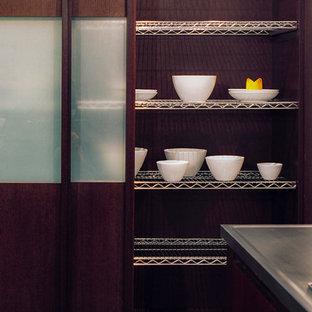 シカゴの中サイズのアジアンスタイルのおしゃれなキッチン (ガラス扉のキャビネット、濃色木目調キャビネット、ステンレスカウンター、ライムストーンの床、アンダーカウンターシンク、グレーのキッチンパネル、石タイルのキッチンパネル、パネルと同色の調理設備) の写真