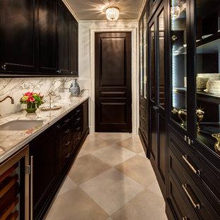 Modelo de cocina de galera, clásica, sin isla, con fregadero bajoencimera, armarios con paneles empotrados, puertas de armario negras, encimera de mármol, salpicadero de mármol, suelo beige, despensa, salpicadero verde y encimeras grises
