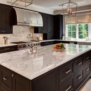 Klassische Küche in L-Form mit Landhausspüle, Schrankfronten mit vertiefter Füllung, schwarzen Schränken, Marmor-Arbeitsplatte, Küchenrückwand in Grau, Rückwand aus Marmor, Küchengeräten aus Edelstahl und grauer Arbeitsplatte in Houston