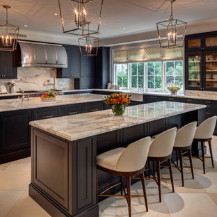 Traditional l-shaped kitchen in Houston with a farmhouse sink, recessed-panel cabinets, black cabinets, white splashback, multiple islands, beige floor, marble benchtops, marble splashback, stainless steel appliances and grey benchtop.