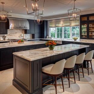 Klassische Küche in L-Form mit Landhausspüle, Schrankfronten mit vertiefter Füllung, schwarzen Schränken, Küchenrückwand in Weiß, zwei Kücheninseln, beigem Boden, Marmor-Arbeitsplatte, Rückwand aus Marmor, Küchengeräten aus Edelstahl und grauer Arbeitsplatte in Houston