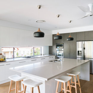 Design ideas for a mid-sized contemporary l-shaped open plan kitchen in Brisbane with an undermount sink, flat-panel cabinets, white cabinets, quartz benchtops, stainless steel appliances, with island, white benchtop, window splashback, medium hardwood floors and brown floor.