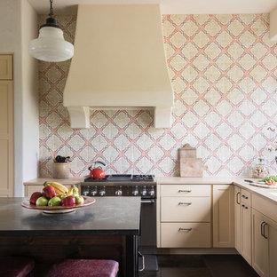 Lantlig inredning av ett l-kök, med en undermonterad diskho, beige skåp, flerfärgad stänkskydd, rostfria vitvaror och en köksö