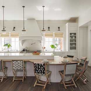 Coastal eat-in kitchen ideas - Example of a beach style l-shaped dark wood floor and brown floor eat-in kitchen design in Charleston with recessed-panel cabinets, white cabinets, white backsplash, stainless steel appliances, an island and white countertops