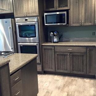 他の地域の中サイズのシャビーシック調のおしゃれなキッチン (アンダーカウンターシンク、シェーカースタイル扉のキャビネット、グレーのキャビネット、ラミネートカウンター、青いキッチンパネル、モザイクタイルのキッチンパネル、シルバーの調理設備、クッションフロア) の写真