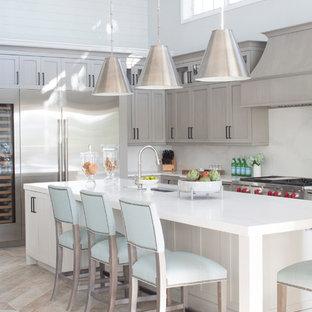 Idee per una cucina a L stile marinaro con lavello sottopiano, ante in stile shaker, ante grigie, paraspruzzi bianco, elettrodomestici in acciaio inossidabile, isola, pavimento beige e top bianco