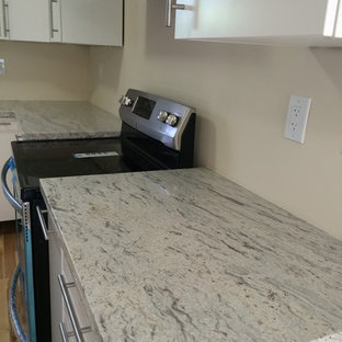 Example of a trendy u-shaped kitchen design in Miami with white cabinets, granite countertops, stainless steel appliances and a double-bowl sink