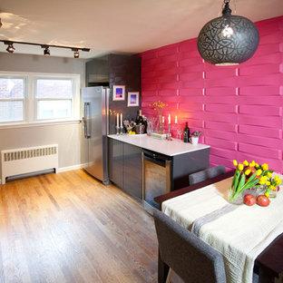 Modern inredning av ett kök och matrum, med släta luckor, grå skåp, rosa stänkskydd och rostfria vitvaror