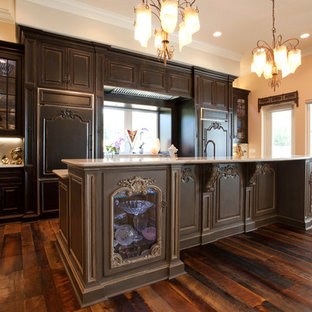 Southwestern open concept kitchen photos - Example of a southwest single-wall dark wood floor open concept kitchen design in Orlando with raised-panel cabinets, dark wood cabinets, granite countertops, colored appliances and an island