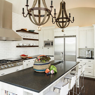 Example of a large trendy u-shaped dark wood floor and brown floor enclosed kitchen design in Portland with white cabinets, white backsplash, subway tile backsplash, stainless steel appliances, an undermount sink, recessed-panel cabinets, granite countertops and an island