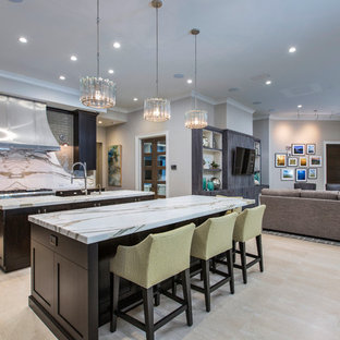 Design ideas for a large contemporary galley open plan kitchen in Jacksonville with shaker cabinets, dark wood cabinets, grey splashback, stainless steel appliances, light hardwood floors and multiple islands.