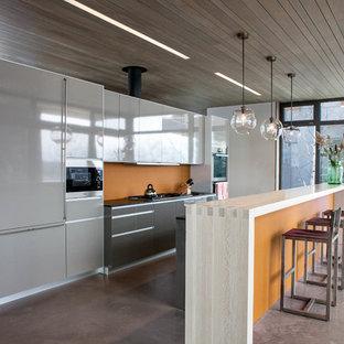 ニューヨークのコンテンポラリースタイルのおしゃれなII型キッチン (フラットパネル扉のキャビネット、グレーのキャビネット、オレンジのキッチンパネル、パネルと同色の調理設備) の写真