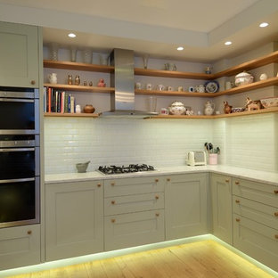 Small scandinavian u-shaped separate kitchen in London with an integrated sink, shaker cabinets, green cabinets, marble benchtops, white splashback, subway tile splashback, stainless steel appliances, light hardwood floors and no island.