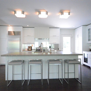 Design ideas for a large midcentury l-shaped open plan kitchen in Grand Rapids with an undermount sink, shaker cabinets, white cabinets, concrete benchtops, stainless steel appliances, dark hardwood floors and with island.