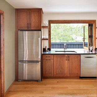 Diseño de cocina rural, pequeña, sin isla, con electrodomésticos de acero inoxidable, suelo de madera clara, fregadero bajoencimera, armarios estilo shaker, puertas de armario de madera oscura y salpicadero de vidrio
