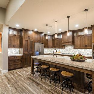 Große, Offene Urige Küche in L-Form mit Schrankfronten im Shaker-Stil, dunklen Holzschränken, Granit-Arbeitsplatte, Küchenrückwand in Grau, Rückwand aus Stäbchenfliesen, Küchengeräten aus Edelstahl, Porzellan-Bodenfliesen, Kücheninsel und Waschbecken in Salt Lake City