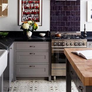 Idéer för ett avskilt, mellanstort klassiskt l-kök, med en rustik diskho, skåp i shakerstil, grå skåp, bänkskiva i täljsten, svart stänkskydd, rostfria vitvaror, en köksö och stänkskydd i stenkakel