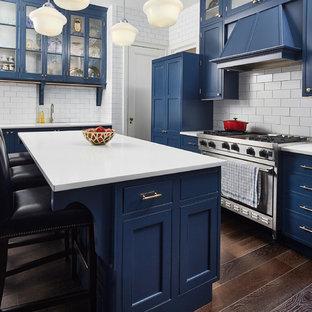Idéer för mellanstora funkis u-kök, med en undermonterad diskho, luckor med infälld panel, blå skåp, bänkskiva i kvartsit, vitt stänkskydd, stänkskydd i tunnelbanekakel, rostfria vitvaror, mörkt trägolv, en köksö och brunt golv
