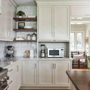 Geschlossene, Mittelgroße Klassische Küche mit Kassettenfronten, beigen Schränken, Quarzit-Arbeitsplatte, Küchenrückwand in Weiß, Rückwand aus Terrakottafliesen, Küchengeräten aus Edelstahl, braunem Holzboden, Kücheninsel, braunem Boden und beiger Arbeitsplatte in Richmond