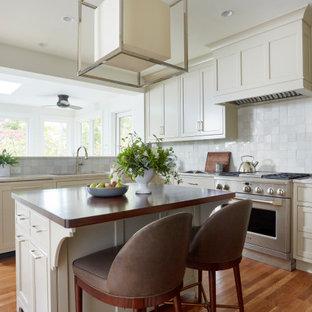 Exempel på ett avskilt, mellanstort klassiskt beige beige u-kök, med en undermonterad diskho, luckor med profilerade fronter, beige skåp, bänkskiva i kvartsit, vitt stänkskydd, stänkskydd i terrakottakakel, rostfria vitvaror, mellanmörkt trägolv, en köksö och brunt golv