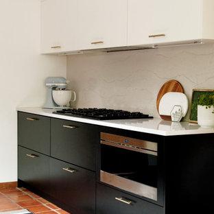 シカゴの中くらいのミッドセンチュリースタイルのおしゃれなキッチン (アンダーカウンターシンク、フラットパネル扉のキャビネット、黒いキャビネット、クオーツストーンカウンター、白いキッチンパネル、クオーツストーンのキッチンパネル、黒い調理設備、テラコッタタイルの床、赤い床、白いキッチンカウンター) の写真