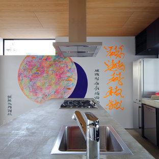 京都のアジアンスタイルのおしゃれなキッチン (一体型シンク、フラットパネル扉のキャビネット、黒いキャビネット、コンクリートカウンター、ガラスまたは窓のキッチンパネル、シルバーの調理設備の、グレーのキッチンカウンター) の写真
