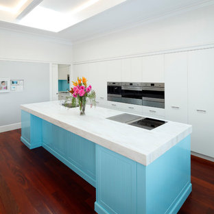 Large contemporary galley kitchen in Sydney with an undermount sink, blue cabinets, stainless steel appliances, dark hardwood floors, with island, red floor, white benchtop and flat-panel cabinets.