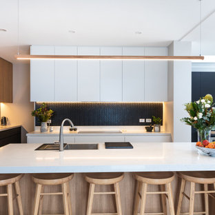 This is an example of a large contemporary kitchen in Sydney with a drop-in sink, flat-panel cabinets, quartz benchtops, black splashback, mosaic tile splashback, black appliances, light hardwood floors, with island and white benchtop.