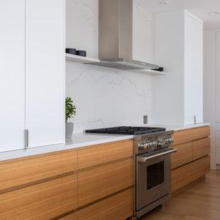 Bild på ett stort funkis vit vitt kök, med en undermonterad diskho, släta luckor, skåp i ljust trä, bänkskiva i kvarts, vitt stänkskydd, stänkskydd i sten, rostfria vitvaror, ljust trägolv och en köksö