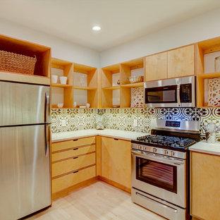 ミルウォーキーの中くらいのモダンスタイルのおしゃれなキッチン (アンダーカウンターシンク、フラットパネル扉のキャビネット、淡色木目調キャビネット、クオーツストーンカウンター、黒いキッチンパネル、テラコッタタイルのキッチンパネル、シルバーの調理設備、淡色無垢フローリング、アイランドなし、茶色い床、白いキッチンカウンター) の写真