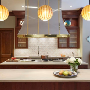 Photo of an expansive transitional galley eat-in kitchen in Chicago with glass-front cabinets, dark wood cabinets, beige splashback, multiple islands, an undermount sink, soapstone benchtops, ceramic splashback, stainless steel appliances and terra-cotta floors.