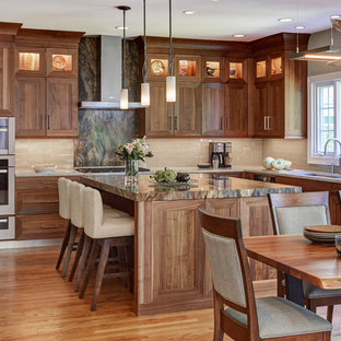 Inspiration for a traditional l-shaped eat-in kitchen in Chicago with an undermount sink, medium wood cabinets, beige splashback, glass tile splashback, stainless steel appliances, medium hardwood floors, with island and orange floor.