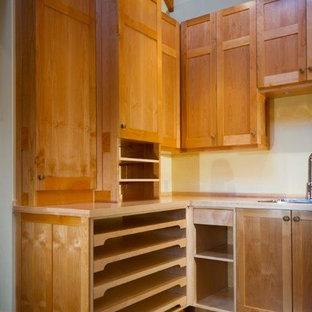 バンクーバーの中サイズのラスティックスタイルのおしゃれなキッチン (ドロップインシンク、シェーカースタイル扉のキャビネット、淡色木目調キャビネット、木材カウンター、スレートの床) の写真