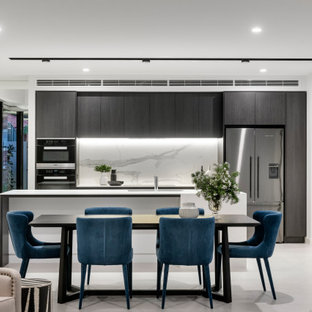Mid-sized contemporary galley eat-in kitchen in Perth with an undermount sink, flat-panel cabinets, dark wood cabinets, white splashback, stainless steel appliances, with island, white floor and white benchtop.