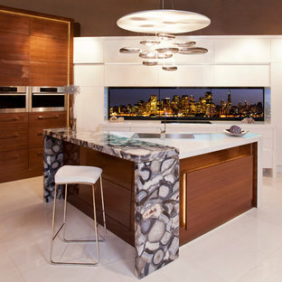 Mid-sized modern l-shaped eat-in kitchen in Toronto with an undermount sink, medium wood cabinets, marble benchtops, stainless steel appliances, marble floors, with island, flat-panel cabinets and multi-coloured splashback.