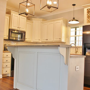 Photo of a mid-sized arts and crafts l-shaped eat-in kitchen in Birmingham with a double-bowl sink, raised-panel cabinets, white cabinets, limestone benchtops, white splashback, subway tile splashback, white appliances, laminate floors, with island and brown floor.