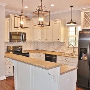 Mid-sized arts and crafts l-shaped eat-in kitchen in Birmingham with a double-bowl sink, raised-panel cabinets, white cabinets, limestone benchtops, white splashback, subway tile splashback, white appliances, laminate floors, with island and brown floor.