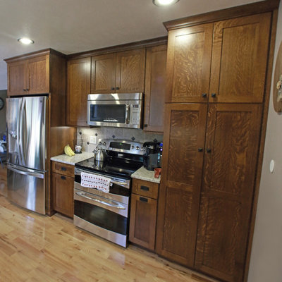 Small farmhouse l-shaped light wood floor and yellow floor eat-in kitchen photo in Other with a farmhouse sink, shaker cabinets, brown cabinets, granite countertops, beige backsplash, ceramic backsplash, stainless steel appliances and a peninsula