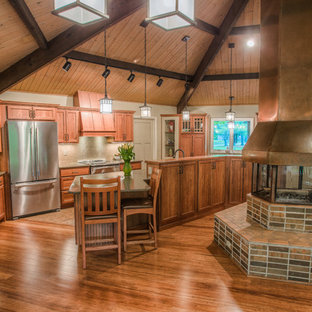 This is an example of a large arts and crafts galley kitchen in Other with an undermount sink, medium wood cabinets, granite benchtops, beige splashback, stainless steel appliances, terra-cotta floors, with island, recessed-panel cabinets, glass tile splashback and brown floor.