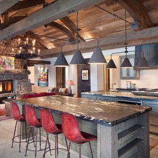 Aménagement d'une grand cuisine ouverte montagne avec un évier 1 bac, un placard avec porte à panneau encastré, des portes de placard en bois vieilli, une crédence blanche et 2 îlots.