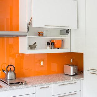 На фото: кухня среднего размера в стиле модернизм с обеденным столом, двойной раковиной, плоскими фасадами, белыми фасадами, столешницей из кварцевого композита, оранжевым фартуком, фартуком из стекла, техникой из нержавеющей стали, пробковым полом и полуостровом с