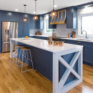 Large transitional enclosed kitchen designs - Enclosed kitchen - large transitional l-shaped medium tone wood floor and brown floor enclosed kitchen idea in Other with recessed-panel cabinets, blue cabinets, stainless steel appliances, an island, a double-bowl sink, marble countertops, white backsplash and marble backsplash