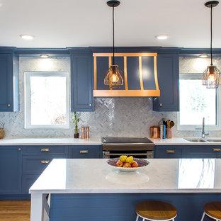 Idéer för ett avskilt, stort klassiskt l-kök, med en dubbel diskho, luckor med infälld panel, blå skåp, marmorbänkskiva, vitt stänkskydd, stänkskydd i marmor, rostfria vitvaror, mellanmörkt trägolv, en köksö och brunt golv