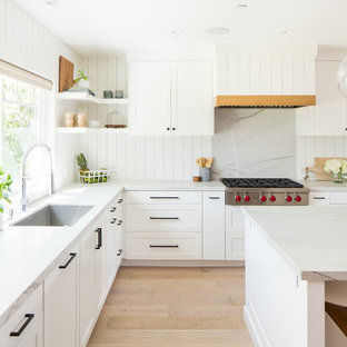 This is an example of a traditional l-shaped kitchen/diner in Orange County with a submerged sink, shaker cabinets, white cabinets, quartz worktops, white splashback, wood splashback, integrated appliances, light hardwood flooring, an island and white worktops.