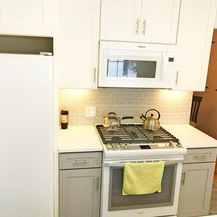 デトロイトの中くらいのトラディショナルスタイルのおしゃれなキッチン (アンダーカウンターシンク、シェーカースタイル扉のキャビネット、グレーのキャビネット、御影石カウンター、グレーのキッチンパネル、サブウェイタイルのキッチンパネル、白い調理設備、セラミックタイルの床、グレーの床、白いキッチンカウンター) の写真