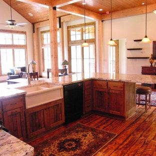 Foto di una grande cucina abitabile stile rurale con lavello stile country, ante a filo, ante in legno scuro, top in granito, elettrodomestici neri, pavimento in legno massello medio e nessuna isola