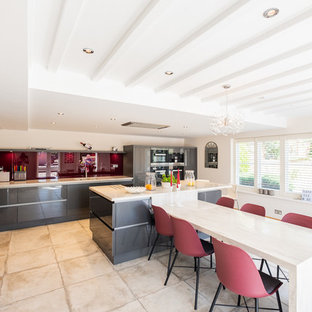 Large contemporary eat-in kitchen in Wiltshire with flat-panel cabinets, grey cabinets, solid surface benchtops, pink splashback, glass sheet splashback, with island, beige benchtop and beige floor.