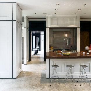 Foto di una grande cucina contemporanea con elettrodomestici in acciaio inossidabile, lavello da incasso, ante con riquadro incassato, ante bianche, top in granito, paraspruzzi grigio, paraspruzzi con piastrelle di metallo, pavimento in cemento, isola e pavimento grigio