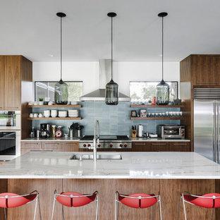 オースティンの中サイズのコンテンポラリースタイルのおしゃれなキッチン (アンダーカウンターシンク、フラットパネル扉のキャビネット、濃色木目調キャビネット、青いキッチンパネル、シルバーの調理設備の、コンクリートの床、大理石カウンター、石タイルのキッチンパネル、グレーの床) の写真